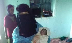 Midwife Lena Al-Shurmani holds Abia's newborn baby shortly after delivery. Abia lost a lot of blood during childbirth. © UNFPA Yemen
